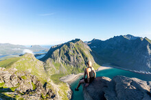 Woman Admiring View While Sitting On Mountain Peak At Ryten, Lofoten, Norway