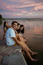 Smiling Family Dangling Legs While Sitting On Retaining During Sunset