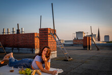 Brunette Woman Eating Fruits, Having A Rooftop Picnic At Sunset Sunset