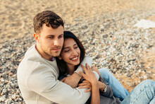 Young Couple Embracing While Sitting On Sand At Beach