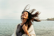 Carefree Woman With Tousled Hair Against Sky At Beach