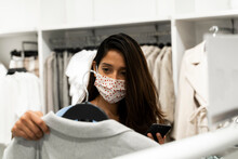 Woman Wearing Protective Mask While Looking At Clothes In Shopping Mall