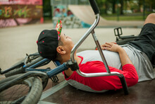 Young Man Resting On BMX Bicycle At Skateboard Park