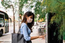 Woman In Face Mask Purchasing Bus Ticket During COVID-19