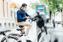 Young Man Using Smart Phone For Payment Of Electric Bicycle At Parking Station During Pandemic