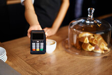 Midsection Of Waitress With Credit Card Reader At Cafe