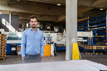 Confident Businessman With Hands In Pockets Standing By Table At Factory