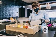 Female Chef Arranging Take Out Food In Cardboard Box At Restaurant Counter During Pandemic