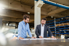 Young And Mature Businessman Working On Blue Print While Standing At Factory