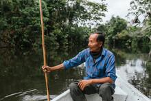 Senior Guarani Man Sitting In Canoe At Napo River, Ecuador