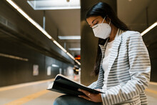 Woman Reading Book On Bench At Metro Station During COVID-19