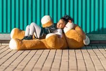 Cute Girl Lying On Teddy Bear Against Green Wall