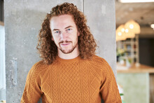 Redhead Hipster Man Standing Against Gray Column At Home