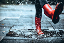 Feet Of Little Girl Wearing Rubber Boots Stepping On Small Puddle