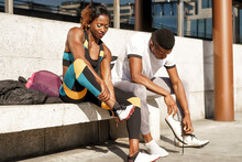 Male And Female Athletes Removing Shoes While Sitting On Bench In City