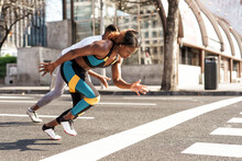 Young Man And Woman Practicing For Sports Race While Running In City