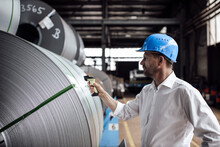 Man Scanning Barcode On Steel Rolls While Standing In Industry