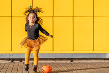Girl With Halloween Headband And Flower Pot Jumping While Playing Against Yellow Checked Pattern Wall