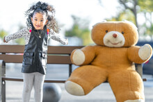 Playful Girl Jumping While Playing With Teddy Bear On Bench In Background