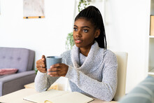 Thoughtful Woman Holding Coffee Cup Looking Away While Sitting In Living Room At Home