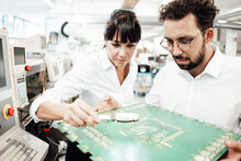 Businesswoman And Businessman Analyzing Large Computer Chip With Magnifying Glass In Industry