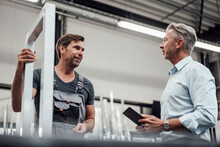 Male Worker And Engineer Discussing Over Metal Frame In Industry
