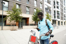 Man Standing With Bicycle Listening Music Through Earphones Standing On Road In City