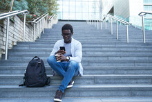 Entrepreneur Using Mobile Phone While Holding Disposable Cup On Staircase At Financial District
