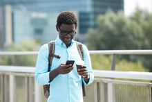 Smiling Man Text Messaging On Smart Phone Standing In City