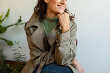 Woman With Hand On Chin Looking Away Sitting Against Wall