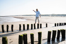 Young Man Walking On Wooden Posts At Beach Against Clear Sky