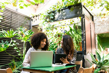 Female Coworkers Smiling Using Laptop And Digital Tablet Sitting In Cafe