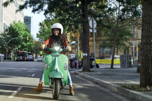 Smiling Young Woman Riding Motor Scooter On Street In City