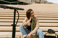 Smiling Woman Talking On Mobile Phone While Sitting By Saxophone Instrument And Electric Push Scooter On Staircase