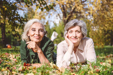 Smiling Women Looking Away While Lying On Grass At Park