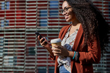 Smiling Woman Using Smart Phone Holding Reusable Cup While Standing By Building