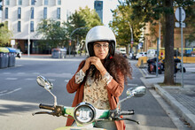 Young Woman Fastening Helmet While Sitting On Motor Scooter In City