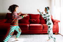 Playful Male And Female Sibling Wearing Headphones Against Sofa In Living Room