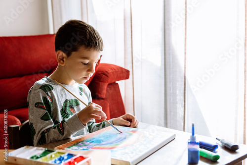 Boy painting over table at home during summer vacation