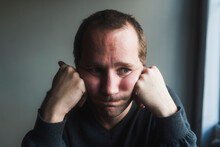 Close-up Of Sad Mid Adult Man With Head In Hands Against Wall At Home