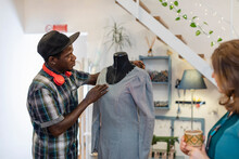 Young Male Designer Trainee Examining Dress On Dummy By Professional At Studio