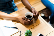High Angle View Of Woman Holding Black Coffee At Table In Cafe