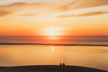 Silhouette Couple Watching Sunset At Atlantic Ocean, Nouvelle-Aquitaine, France