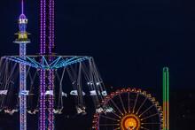 Germany, Bavaria, Munich, Aerial View Of Illuminated Chain Swing Ride And Ferris Wheel At Night