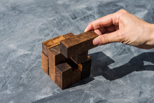 Hand Of Woman Assembling Pieces Of Wooden Puzzle