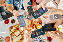 Friends Having Dinner With A Cheese Platter Taking Smartphone Pictures