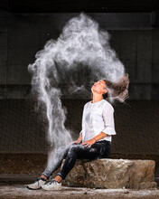 Young Woman Tossing Hair With Flour While Sitting On Rock Against Concrete Wall