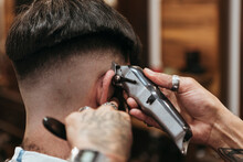 Barber's Hands Using Electric Razor On Man At Hair Salon