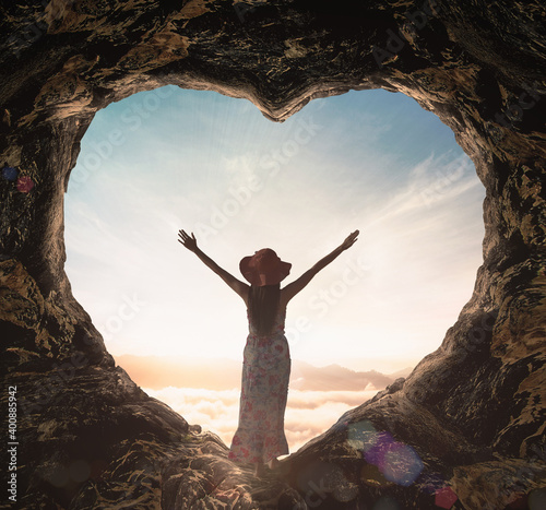 Obraz na plátně Worship God concept: Silhouette alone woman standing on cave of heart and sea of