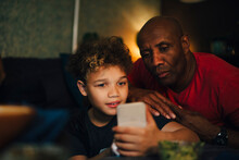 Boy Using Mobile Phone By Father In Living Room At Night